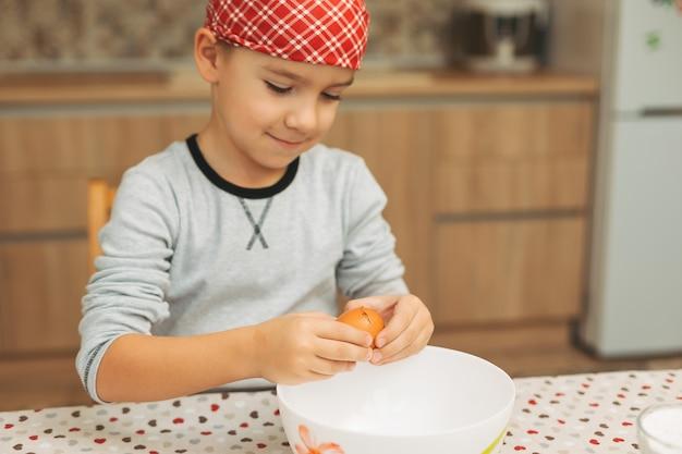 Mały chłopiec gotuje. dziecko łamanie jajka do miski.