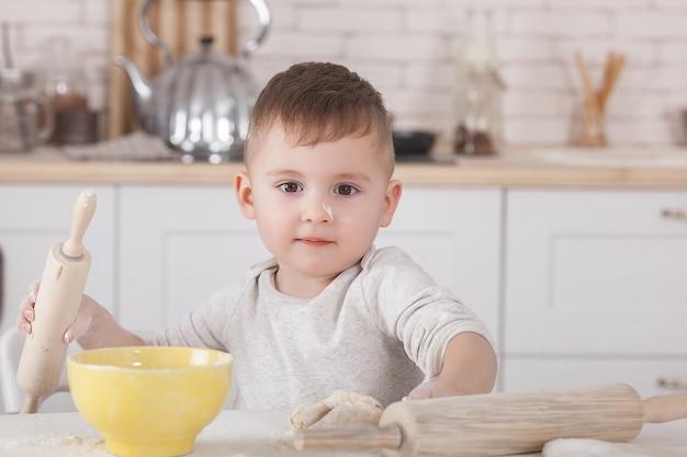 Mały chłopiec gotuje. dziecko w kuchni