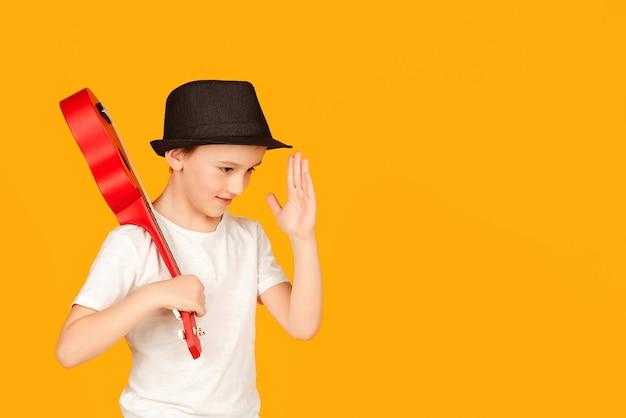 Mały chłopiec gra na hawajskiej gitarze lub ukulele. szczęśliwe dziecko ciesząc się muzyką. uczeń uczący się grać na ukulele. modny chłopak w letnim kapeluszu na białym tle na pomarańczowym tle.