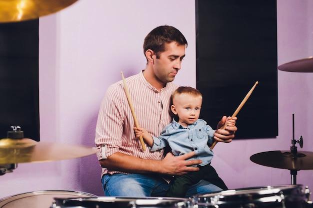 Mały chłopiec gra na perkusji w studio nagrań.