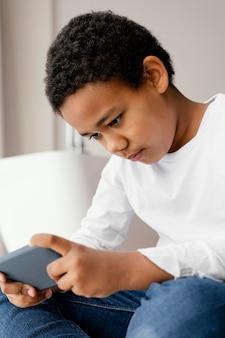 Mały chłopiec gra na telefonie komórkowym