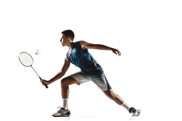 Mały chłopiec gra w badmintona na białym tle.