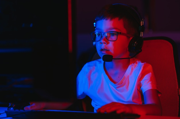 Mały chłopiec gra w grę wideo w ciemnym pokoju