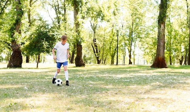 Mały chłopiec gra w piłkę nożną sam z miejsca na kopię