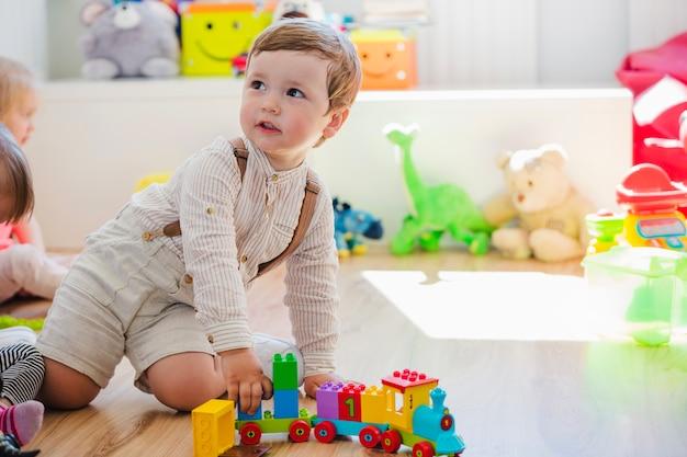 Mały chłopiec gra z pociągu zabawki