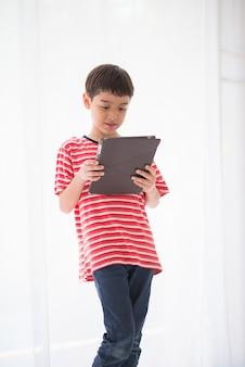 Mały chłopiec grając w tablet w domu