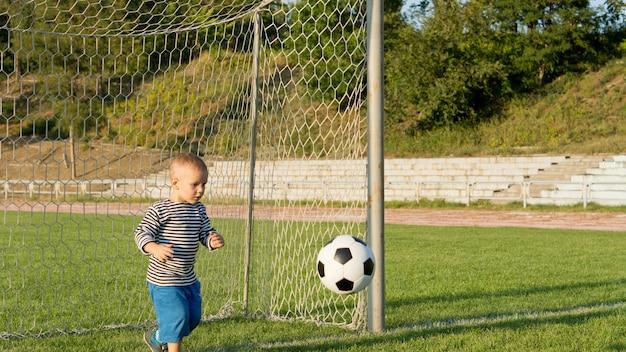Mały chłopiec grający bramkarzem, który mocno koncentruje się na piłce, przygotowując się do obrony bramki na zielonym boisku