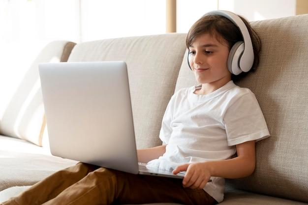 Mały chłopiec grający w grę wideo na swoim laptopie
