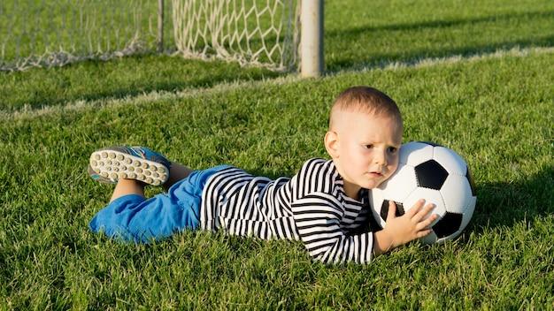Mały chłopiec grający w piłkę nożną w wieczornym świetle leży na brzuchu na trawie, ściskając piłkę, gdy strzela gola