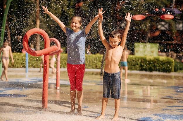 Mały chłopiec i dziewczynka bawić się na wodnym placu zabaw w letnim parku. wypoczynek dzieci w aquaparku, wodna przygoda na wakacjach