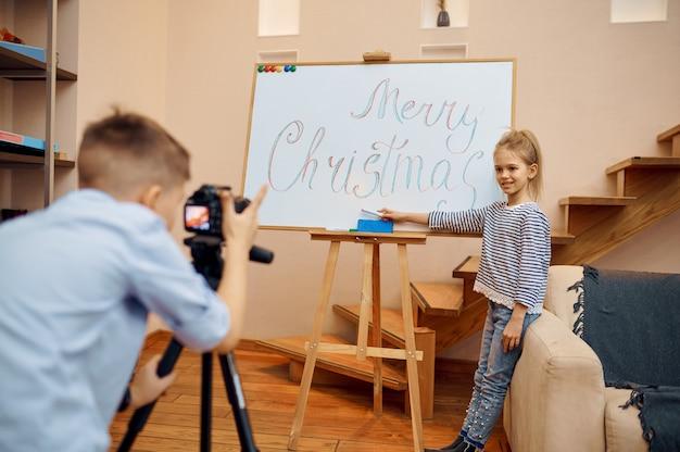 Mały chłopiec i dziewczynka, blogerzy tworzą świątecznego bloga, mali vlogerzy. blogowanie dzieci w domowym studio, media społecznościowe dla młodych odbiorców, transmisja internetowa w internecie