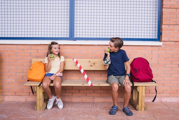 Mały chłopiec i dziewczynka jedzą jabłko w przerwie siedząc na ławce, zachowując dystans społeczny.
