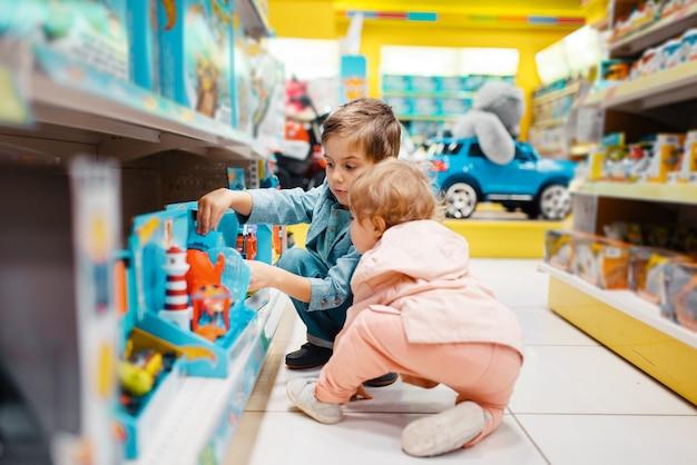 Mały chłopiec i dziewczynka na półce w sklepie dla dzieci, widok z boku.