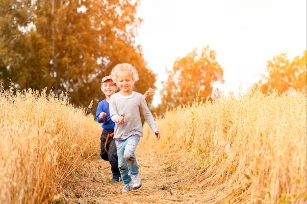 Mały chłopiec i dziewczynka na polu pszenicy w słońcu działa, bawiąc się z przyrodą. dziecko podnoszenie na tle nieba pole i zachód słońca. koncepcja środowiska dzieci