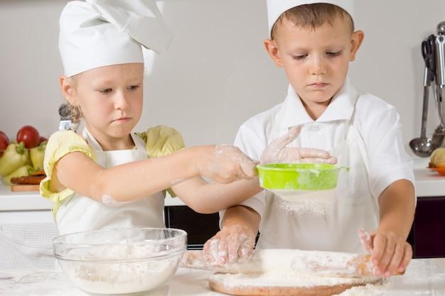 Mały chłopiec i dziewczynka pieką w kuchni