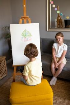 Mały chłopiec i dziewczynka razem rysują za pomocą sztalug w domu