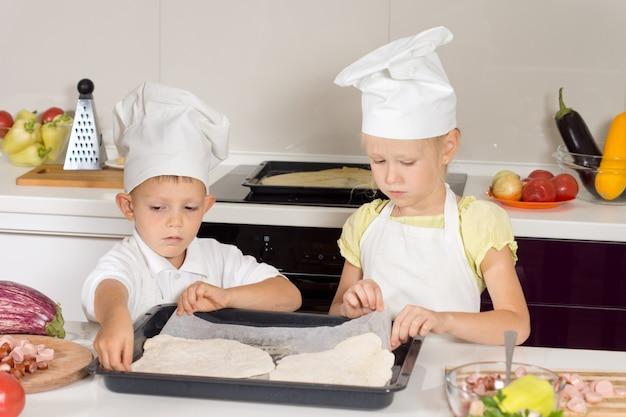 Mały chłopiec i dziewczynka robią domową pizzę?