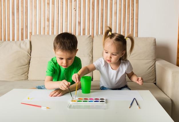 Mały chłopiec i dziewczynka rysują pędzlem i malują na papierze przy stole w pokoju. widok z góry