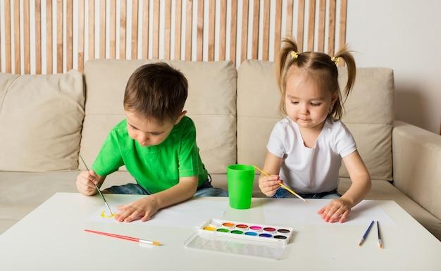Mały chłopiec i dziewczynka rysują pędzlem i malują na papierze przy stole w pokoju