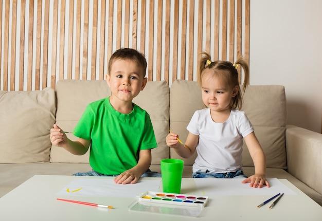 Mały chłopiec i dziewczynka siedzą przy stole i rysują pędzlem i farbami na białym papierze w pokoju