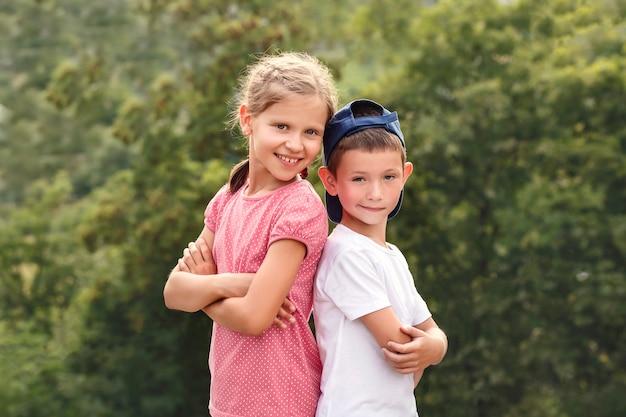 Mały chłopiec i dziewczynka stoją do siebie plecami