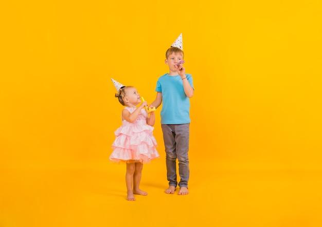 Mały chłopiec i dziewczynka stoją i świętują uroczystość w czapkach i dmuchają w papierowe gwizdki na żółtym tle z kopią miejsca