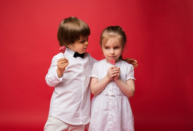 Mały chłopiec i dziewczynka trzymając cukierki na kiju i przytulanie na czerwono z miejscem na tekst