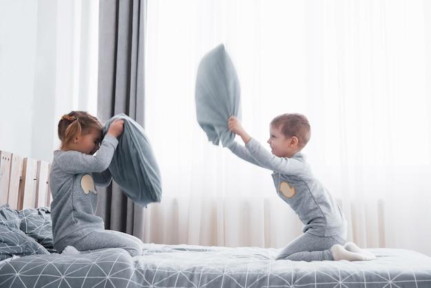 Mały chłopiec i dziewczynka urządzili walkę na poduszki na łóżku w sypialni. niegrzeczne dzieci biją się w poduszki. lubią taką grę.