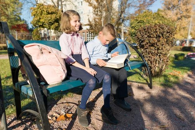 Mały chłopiec i dziewczynka w wieku szkolnym czytanie książki