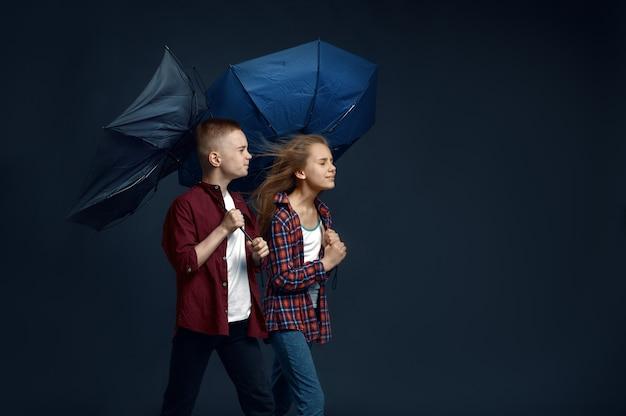 Mały chłopiec i dziewczynka z parasolami w studio