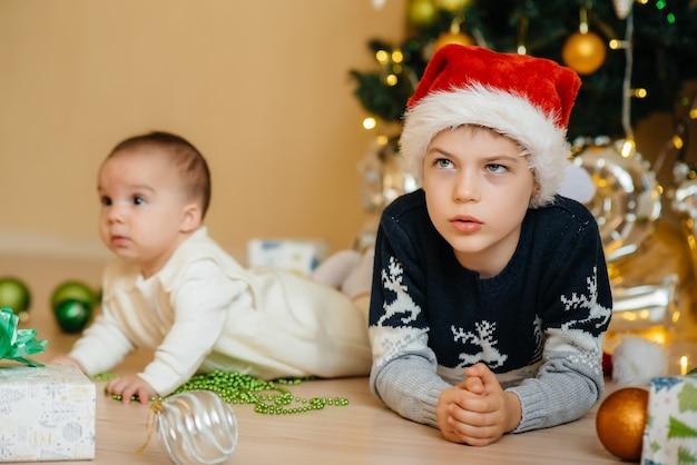 Mały chłopiec i jego brat bawią się prezentami pod świąteczną choinką