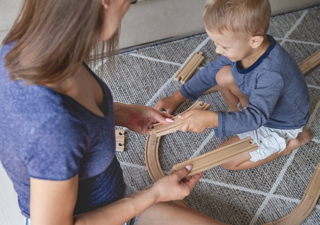 Mały chłopiec i jego matka bawi się koleją, siedząc na podłodze