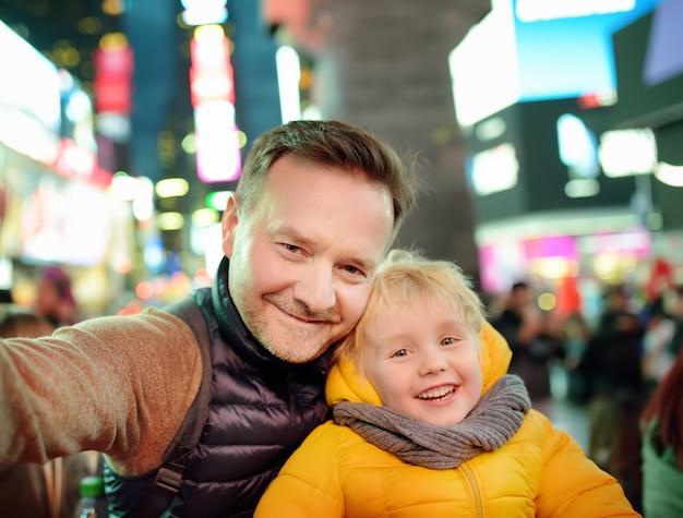 Mały chłopiec i jego ojciec biorąc selfie na times square wieczorem