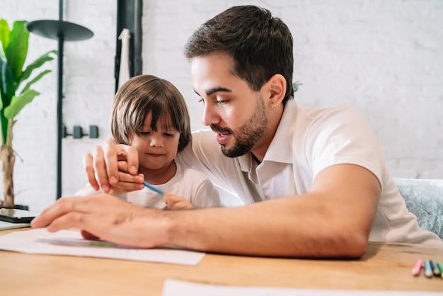 Mały chłopiec i jego ojciec dobrze się bawią razem rysując coś na papierze w domu.