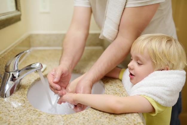 Mały chłopiec i jego ojciec mycie rąk mydłem w łazience razem