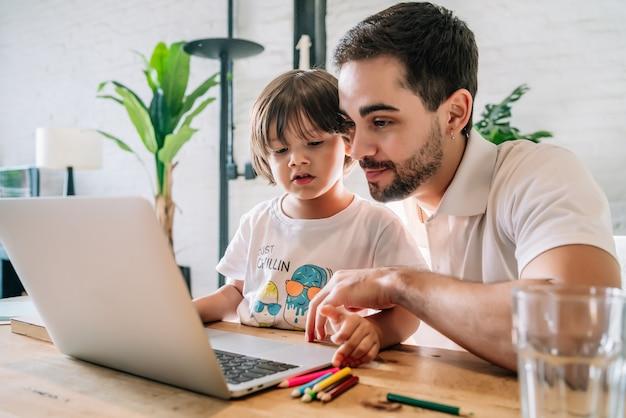 Mały chłopiec i jego ojciec razem za pomocą laptopa podczas pobytu w domu. nowy normalny styl życia. koncepcja jednorodzicielska.