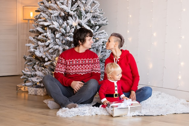 Mały chłopiec i jego rodzice w domu z choinką na tle. szczęśliwy chłopiec bawi się w pobliżu choinki.