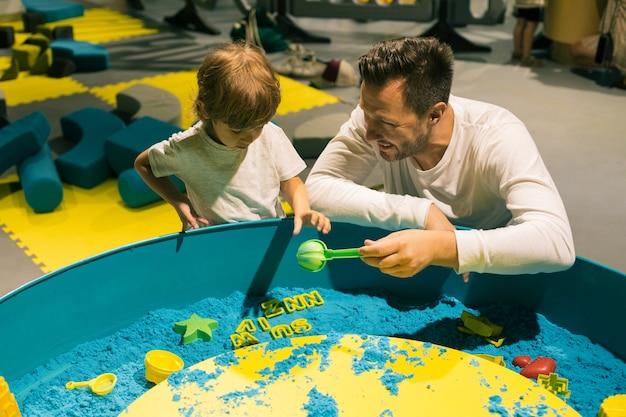 Mały chłopiec i jego tata wybierają formę zabawy z plastikowym piaskiem kinetycznym. rozwój umiejętności motorycznych. łagodzenie stresu i napięcia. kreatywność. wzajemne zrozumienie .
