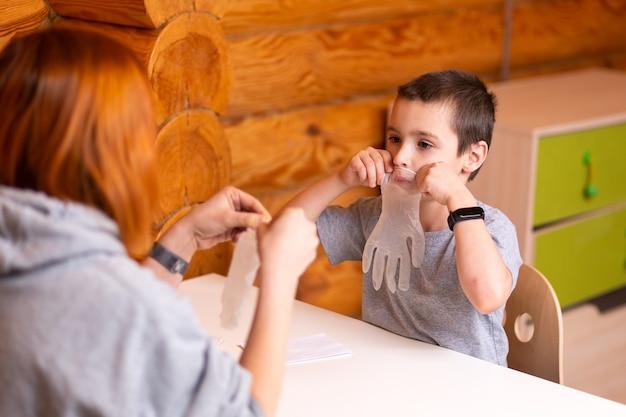 Mały chłopiec i mama bawią się, pompują jednorazowe rękawiczki chirurgiczne i przygotowują się do eksperymentów chemicznych w domu