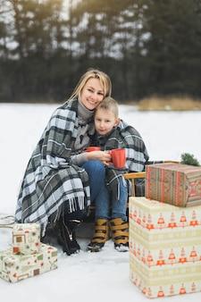 Mały chłopiec i matka przesuwane w zimowym lesie. mama i syn siedzą na sankach