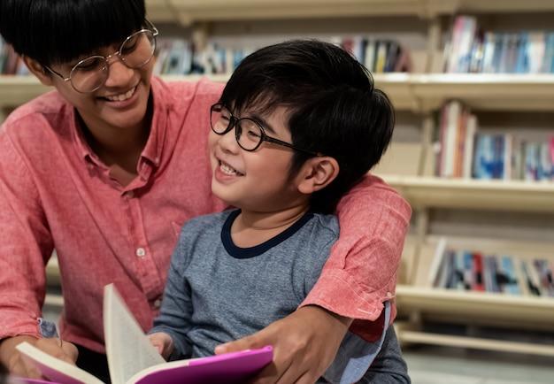 Mały chłopiec i nauczyciel razem czytając książkę, z radością, rozmazane światło wokół
