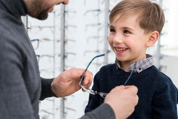 Mały chłopiec i ojciec przymierzający okulary w sklepie