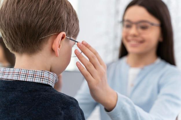 Mały chłopiec i siostra w sklepie przymierzają okulary