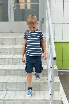 Mały chłopiec idzie samotnie, opuszcza budynek i schodzi po schodach