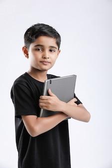 Mały chłopiec indyjski / azjatycki z notatnikiem