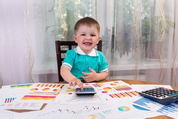 Mały chłopiec jako analityk używający kalkulatora w biurze