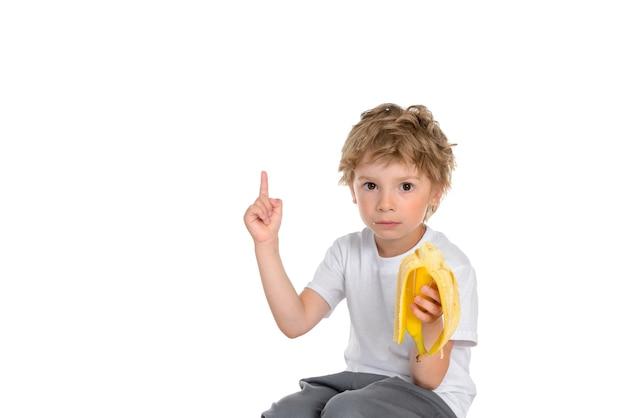 Mały chłopiec je banana, patrzy poważnie i wskazuje w górę