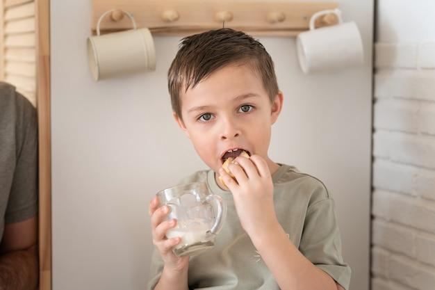 Mały chłopiec je chleb lub kanapkę i pije mleko w kuchni koncepcja porannej rutyny