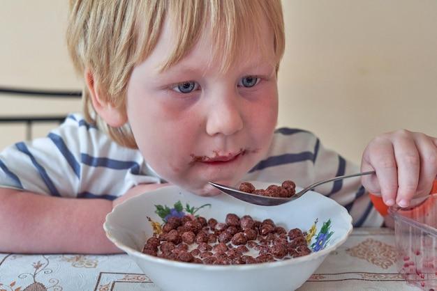 Mały chłopiec je śniadanie z czekoladowymi kulkami z mlekiem