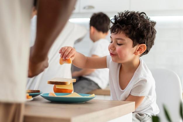 Mały chłopiec je śniadanie z tatą